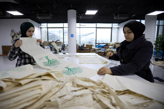 Women work in the creation of tote bags as part of the Teeah project, which aims to promote the reduction of plastic bags use, in Irbid