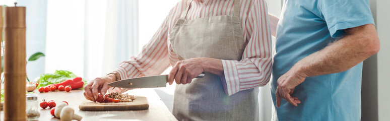 Cropped view of man standing by wife cutting vegetables on kitchen table, panoramic shot