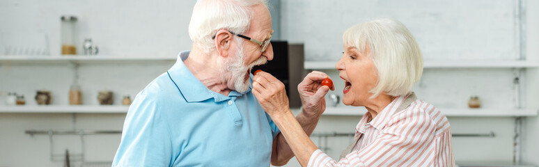 Side view of senior couple feeding each other with cherry tomatoes in kitchen, panoramic shot