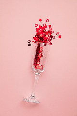 Valentine's day date night background. Drinks glasses with red heart confetti.