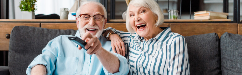 Panoramic shot of senior couple laughing while watching tv on sofa at home Wall mural