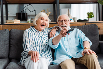 Senior couple laughing while watching tv on couch in living room Wall mural
