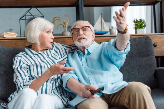 Selective focus of senior man gesturing while watching tv with wife on couch in living room