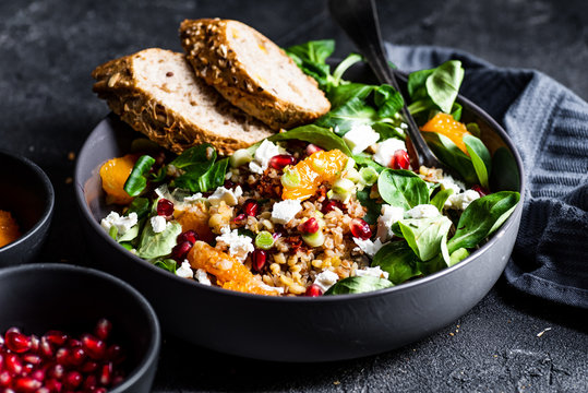 Buckwheat salad with lamb's lettuce, pomegranat seeds, goat cheese, mandarine and spring onion, Served with whole grain baguette and red wine. Black table and black background.