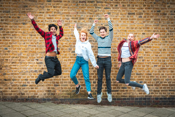 Happy teen friends jumping in front of a wall