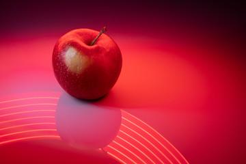 Obraz Czerwone jabło na czerwonym malowanym światłem tle - fototapety do salonu