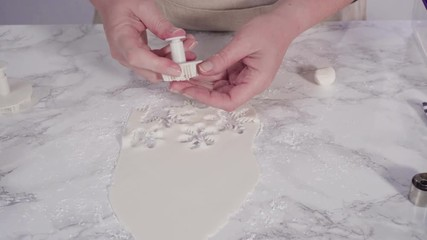 Wall Mural - Step by step. Cutting out snowflakes with cookie cutters out of white fondant on a marble counter.