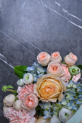 Tuinposter Lelie A bouquet of fresh flowers of roses, anemones and gartensia in on a stone background.
