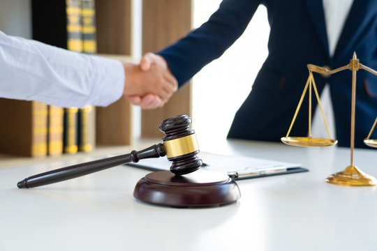 Judge And Client Shaking Hands after agreeing to enter into a contract for a court case In A Courtroom, legal services concept