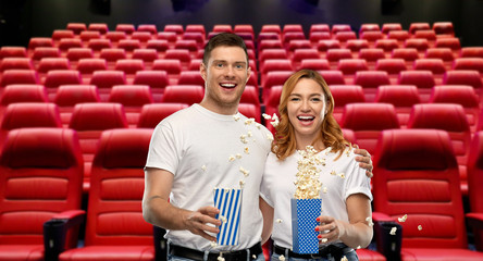 food, entertainment and people concept - portrait of happy couple in white t-shirts eating popcorn over empty cinema hall with red seats on background