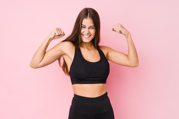 Young caucasian fitness woman doing sport isolated showing strength gesture with arms, symbol of...