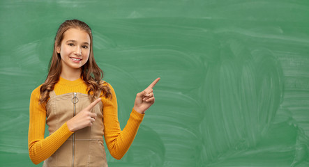 school, education and learning concept - smiling teenage student girl pointing fingers up girl over green chalkboard background