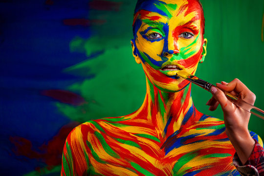 Color art face and body painting on woman for inspiration. Abstract portrait of the bright beautiful girl with colorful make-up and bodyart.