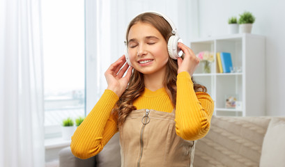 audio, technology and people concept - smiling teenage girl in headphones listening to music over...
