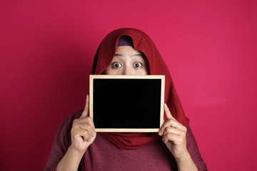 Muslim woman wearing hijab covering her face with blackboard, anonymouse facial expression, blank...