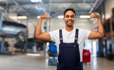 service, profession and gesture concept - happy smiling indian mechanic showing his power over car shop background