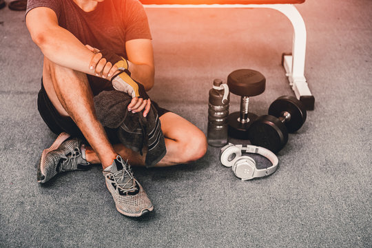 muscular caucasian young  man taking a break relax  after workout for good healthy in fitness gym. sport exercise concept