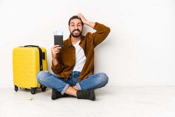 Young caucasian man sitting holding a passport and a suitcase isolated being shocked, she has remembered important meeting.