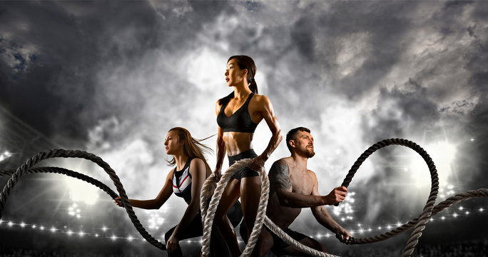 Sporty woman and man working out with battle ropes. Sports banner.