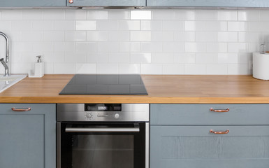 interior and cooking concept - modern kitchen counter with built in oven and electric hob at home