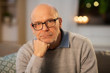 old age and people concept - sad senior man in glasses thinking at home in evening