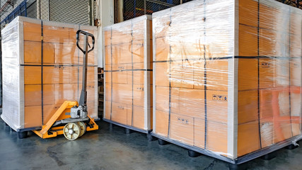 stack cardboard boxes wrapping plastic on pallets and hand pallet truck for export shipment, warehouse industry logistics, cargo transport Wall mural