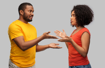 relationships and people concept - unhappy african american couple having argument over grey...