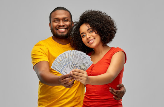 finance, saving and people concept - happy smiling african american couple with dollar money over grey background
