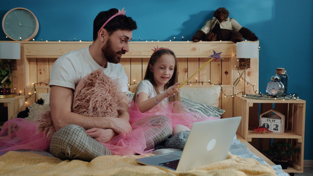 Fairytale family party at home. View of happy father and daughter playing fairies waving with magic wand looking on laptop screen sitting on bed and having fun.