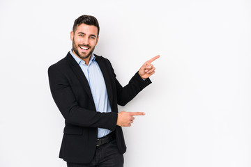 Young caucasian business man against a white background isolated excited pointing with forefingers...
