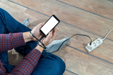 Electricity dependence concept. Man holding phone connected to a power strip