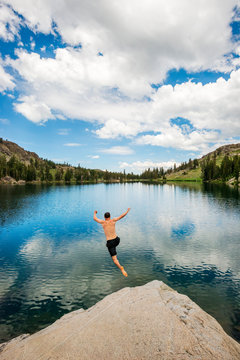 A man jumps off a rock into Emigrant Lake in the summer near Carson Pass and Kirkwood, California
