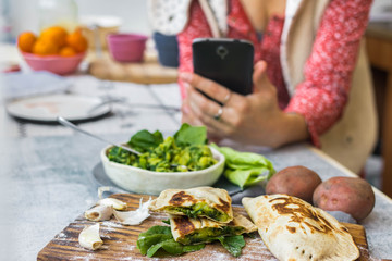 Woman take picture of vegan food with phone at her kitchen. Hand make a closeup smartphone photo of green salad and stuffed bread for blogging or social media content. Vegetarian healthy food.