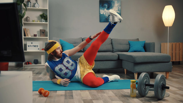 Funny fitness vlogger exercising and training at home. Sportive young man in retro clothes shooting a sports vlog. Motivation and sport concept.