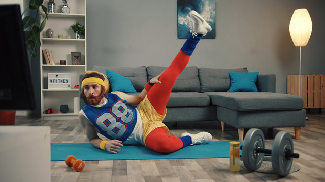 LOS ANGELES, CALIFORNIA, 10 OCTOBER, 2019: Funny fitness vlogger exercising and training at home. Sportive young man in retro clothes shooting a sports vlog. Motivation and sport concept.