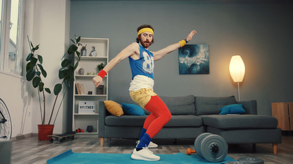 Stupid-looking funny athlete man in retro outfit dancing and warming up having an intense home workout.