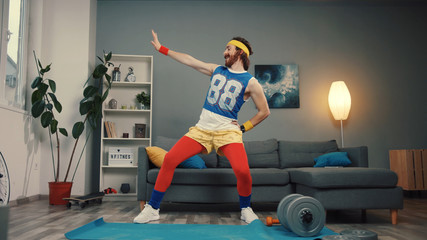 Funny young bearded sportsman dancing with cool energetic moves warming up and exercising at home.