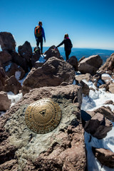 A geological survey marker marks the summit of Lassen Peak (Mount Lassen, 10,457 feet) with hikers standing in the background in Lassen Volcanic National Park, California.