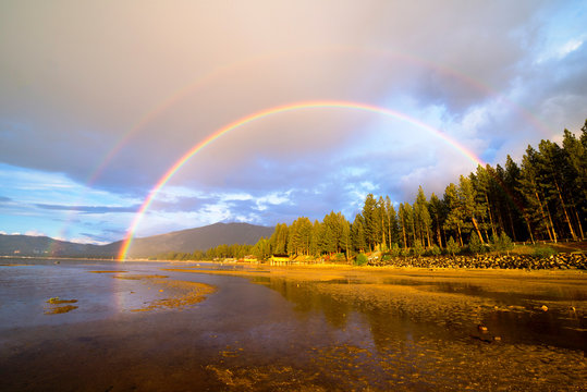 A double rainbow appears after an afternoon thunderstorm over South Lake Tahoe with Heavenly Mountain Resort in the background, California.