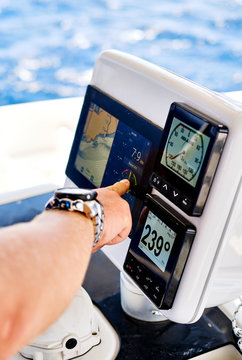 Close up male hand pointing on navigation devices in catamaran deck, adventure recreational sport, yachting concept