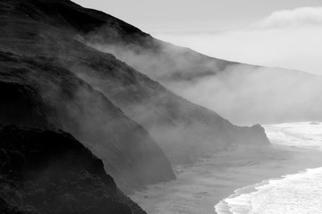 Dramatic fog covers the beach and cliffs of Blind Beach on the Sonoma Coast State Park near Jenner, CA