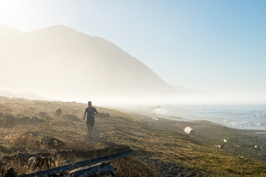 A man trail runs next to the beach in beautiful fog and early morning light near Spanish Creek on the Lost Coast Trail in the King Range National Conservation Area of Northern California.
