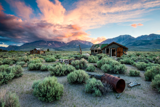 A magnificent sunset explodes over old abandoned cabins in the desert with the Sierra Nevada mountains in the background near Lee Vining, California.