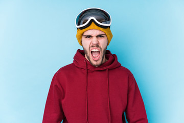 Young caucasian man wearing a ski clothes isolated screaming very angry and aggressive.