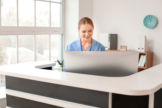 Young female receptionist working at desk in clinic