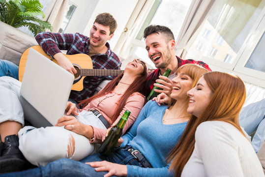 Group of teenagers having fun at home using laptop and playing guitar in living room