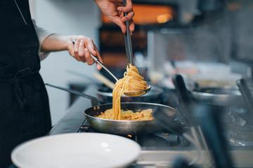 Chef preparing a pasta dish in traditional Italian restaurant kitchen