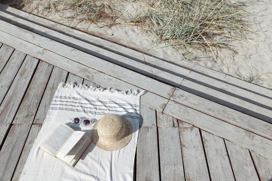Boho eco styled beach essentials on sand by sea