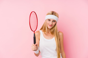 Young blonde woman playing badminton isolated