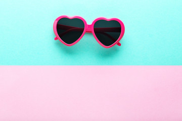 Modern heart shaped sunglasses on colorful background